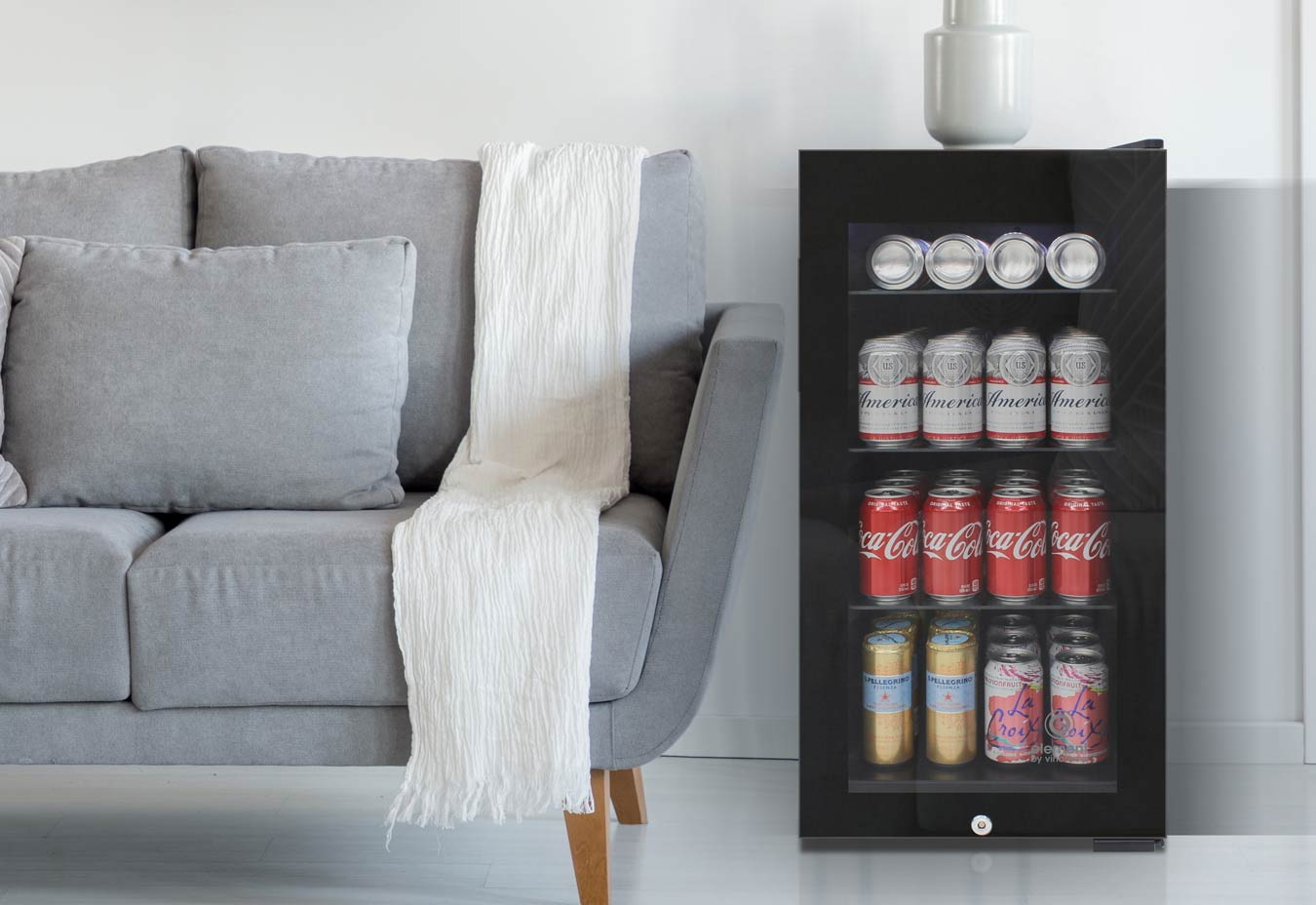 small black fridge next to gray couch